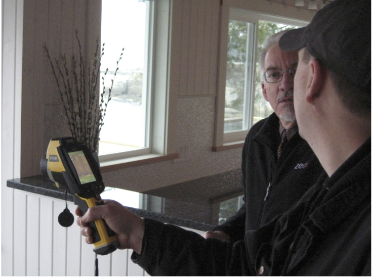 Thermal imaging expert conducting real-time assessment of heat loss with hand-held infrared camera. The householder is actively engaged and immediately understands the heat lost with the images provides.  Photo Credit: Stephen Sheppard