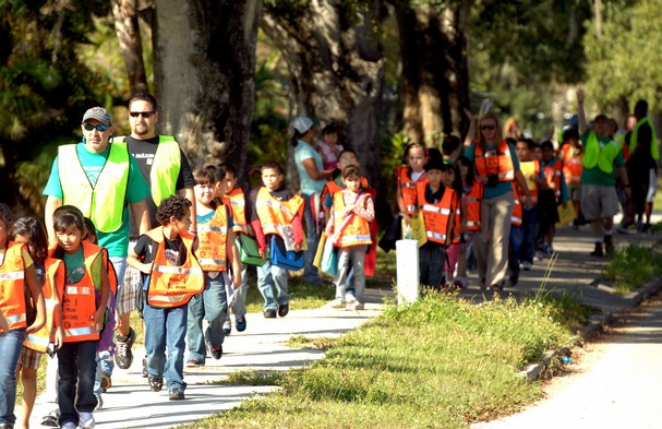 The walking school bus: a great example of initiative taken at the neighbourhood level to reduce car use, resulting in lower carbon emissions and higher community connectivity with the landscape. Source: tcpalm.com.